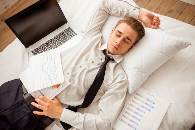 Vista superior do homem de negócios louro novo cansado atrativo.