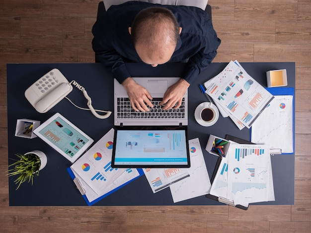 Vista superior do homem de negócios no escritório corporativo, sentado à mesa, digitando no laptop, trabalhando em estatísticas financeiras e estratégia de negócios