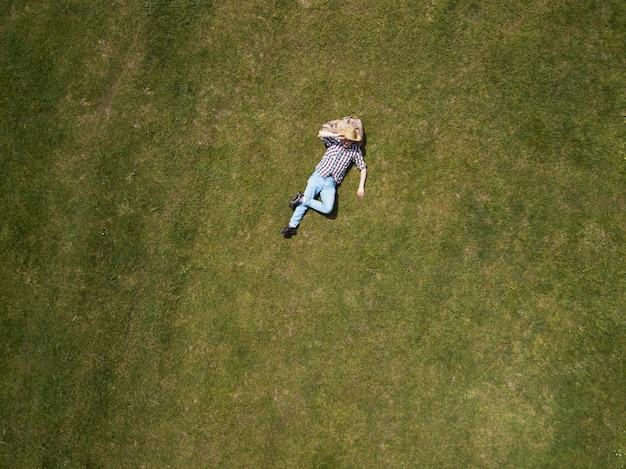 Vista superior do homem feliz, deitado na grama verde