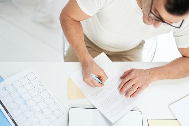 Vista superior do homem latino focado, trabalhando com seu laptop, marcando dias no calendário e fazendo anotações enquanto trabalhava na área de trabalho. trabalhe online, estudando em casa o conceito