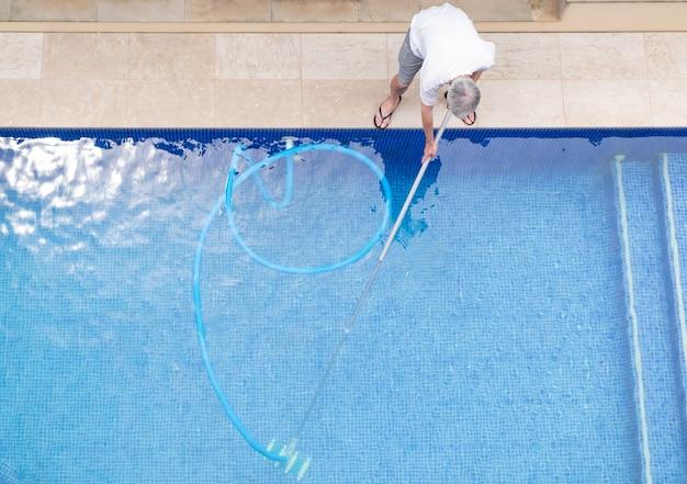 Vista superior do homem limpando uma piscina