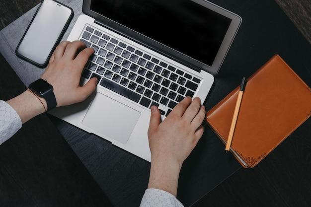 Vista superior do homem mãos digitando em um laptop