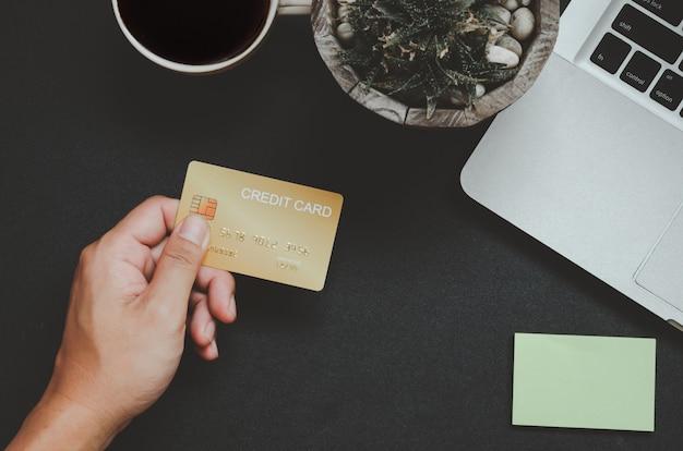 Vista superior do homem segurando um cartão de crédito e na mesa