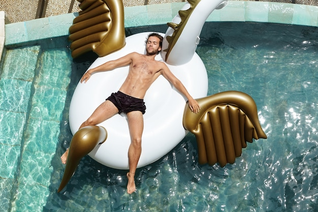 Vista superior do homem sem camisa jovem relaxado e feliz flutuando na piscina, deitado na cama inflável durante suas férias tão esperadas no país tropical.