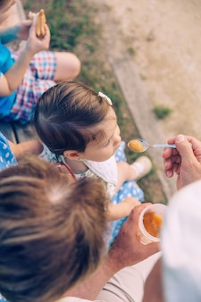 Vista superior do homem sênior alimentando-se com purê de frutas a adorável menina sentada sobre uma mulher sênior em um banco ao ar livre. conceito de estilo de vida de avós e netos.