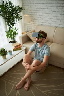 Vista superior do homem sentado no chão da sua sala de estar, desfrutando de um jogo de realidade virtual