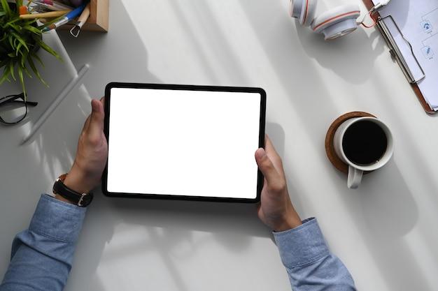 Vista superior do homem sentado no espaço de trabalho e usando o tablet com tela branca para texto de publicidade.