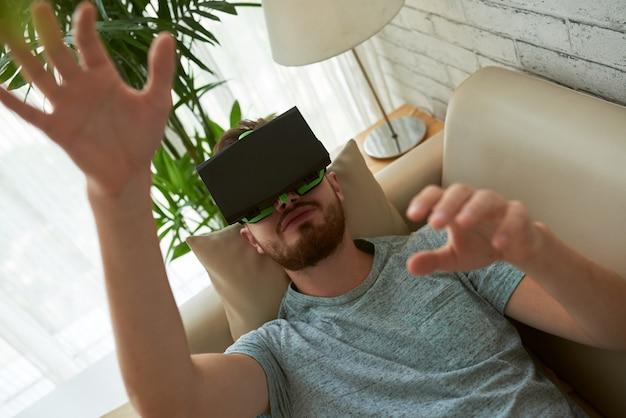 Vista superior do homem testando o aplicativo vr em seu sofá em casa