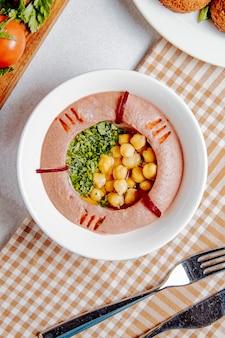 Vista superior do hummus tradicional do oriente médio com grão de bico e azeite