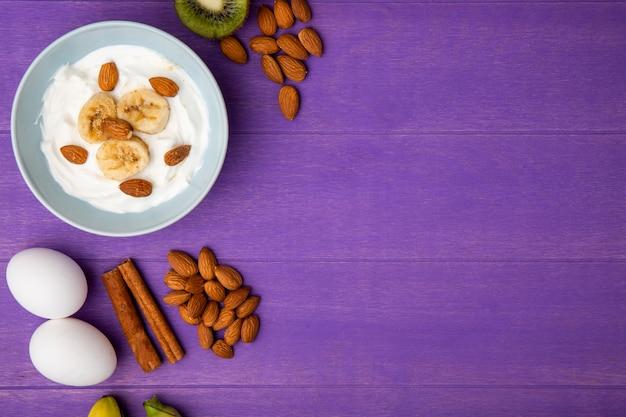 Vista superior do iogurte com bananas fatiadas e amêndoa, kiwi e paus de canela, dois ovos na madeira roxa com espaço de cópia