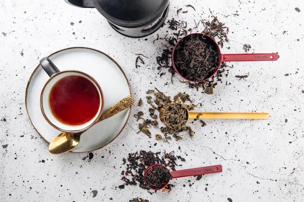 Vista superior do jogo de chá com colheres e uma xícara no fundo branco
