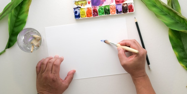 Vista superior do jovem artista profissional pintando no papel de desenho com a cor da água