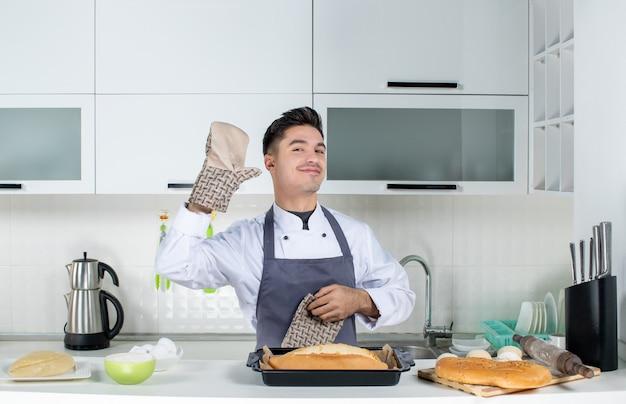 Vista superior do jovem chef masculino feliz de uniforme em pé atrás da mesa usando o suporte