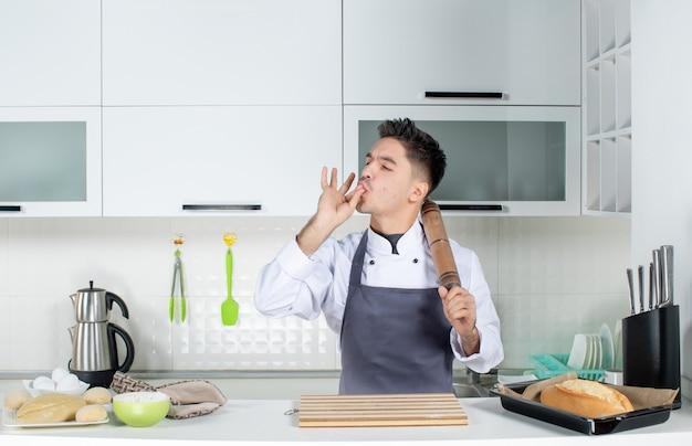 Vista superior do jovem cozinheiro de uniforme em pé atrás da mesa, segurando o ralador e fazendo um gesto perfeito na cozinha branca