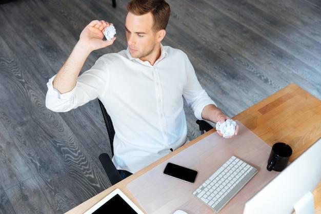 Vista superior do jovem empresário relaxado e sorridente, sentado e usando o smartphone no escritório