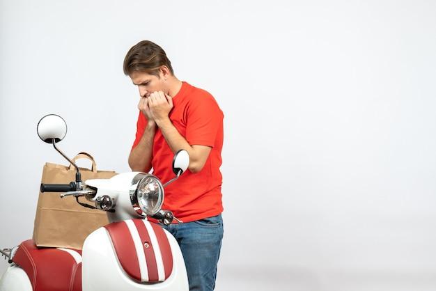 Vista superior do jovem entregador de uniforme vermelho em pé perto da scooter e se sentindo confuso na parede branca