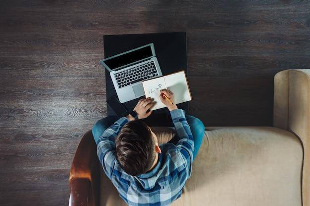 Vista superior do jovem freelancer escrevendo em um caderno enquanto trabalhava em casa