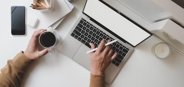 Vista superior do jovem freelancer masculino digitando no computador portátil, mantendo a xícara de café
