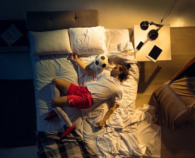 Vista superior do jovem futebol profissional, jogador de futebol dormindo em seu quarto em roupas esportivas com bola