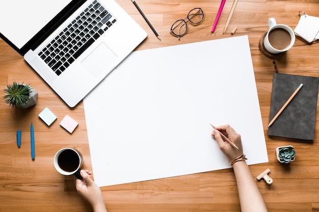 Vista superior do jovem trabalhando na mesa com fundo de espaço em branco. conceitos de plano de negócios ou criatividade