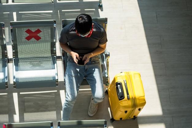 Vista superior do jovem turista com máscara de proteção, sente-se na área de estar perto da bagagem e usando o telefone no terminal do aeroporto.
