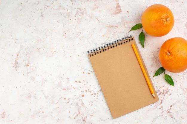 Vista superior do lápis de laranjas frescas no bloco de notas na superfície brilhante com espaço de cópia