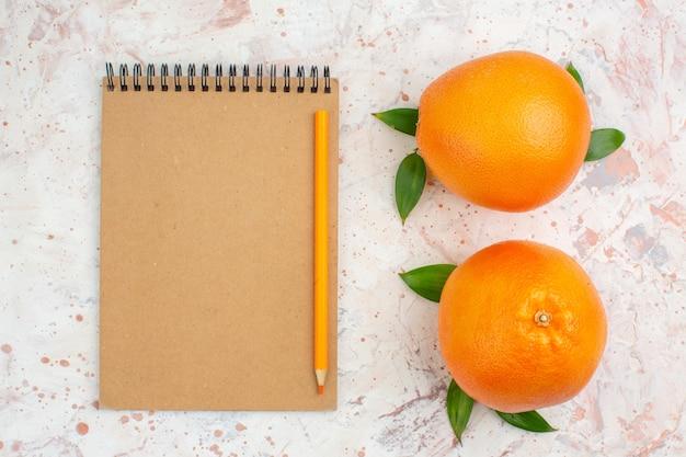 Vista superior do lápis laranja com laranjas frescas no caderno na superfície brilhante e isolada