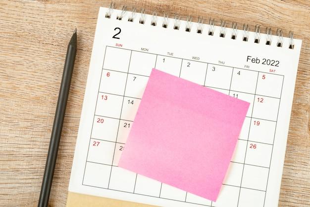 Vista superior do lápis, planejamento do calendário e prazo com nota adesiva no fundo de madeira, mesa do calendário 2022 no mês de fevereiro