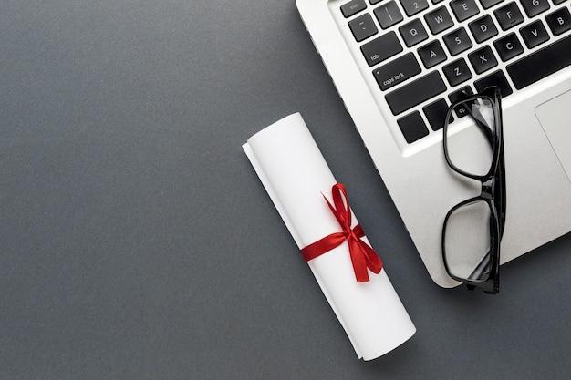 Vista superior do laptop com óculos e diploma