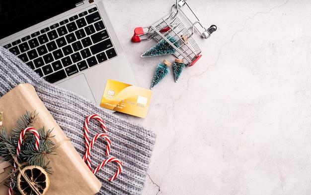 Vista superior do laptop, decorações de natal e carrinho de compras no fundo branco