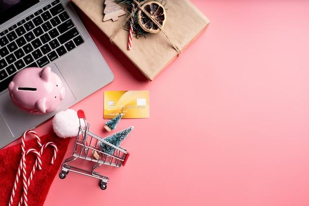 Vista superior do laptop, decorações de natal e cofrinho em fundo rosa