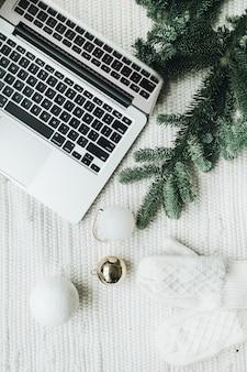 Vista superior do laptop deitado sobre o cobertor branco decorado com um galho de árvore de natal
