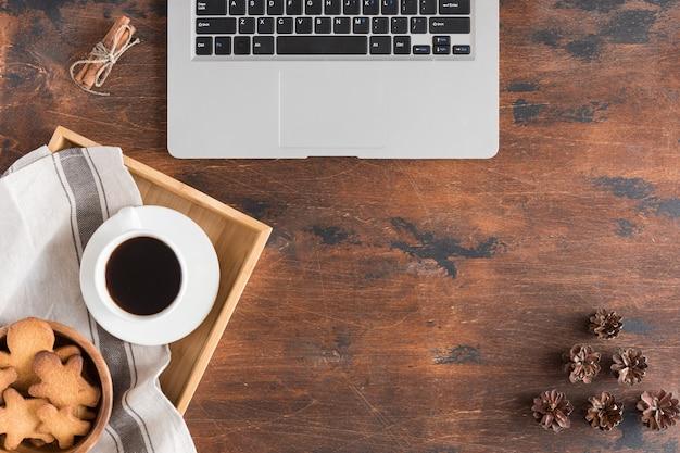 Vista superior do laptop, homem-biscoito, xícara de café no escuro de madeira rústica