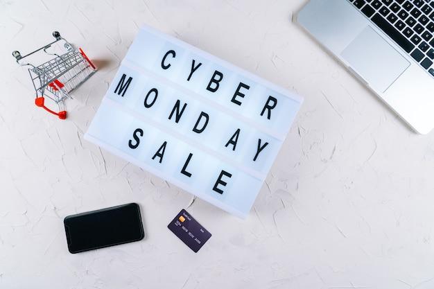 Vista superior do laptop, palavras de venda de promoção cibernética na mesa de luz, caixas de presente, laptop, compras