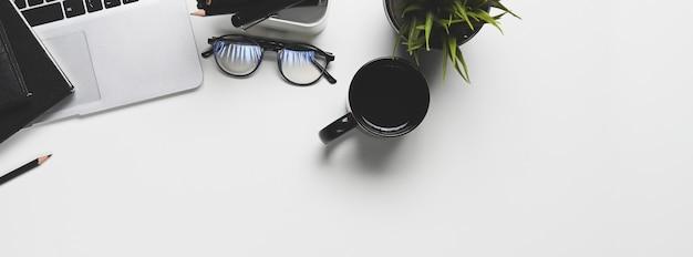 Vista superior do laptop, xícara de café, copos e planta na mesa branca.