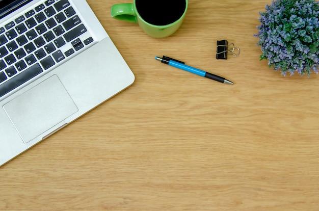 Vista superior do laptop, xícara de café, flor e caneta na mesa de madeira. cópia plana spce.work for home