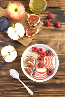 Vista superior do leite de aveia com figos, framboesas e maçã na tigela sobre a mesa de madeira