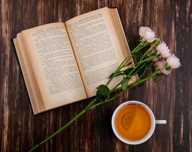 Vista superior do livro aberto com rosas cor de rosa e uma xícara de chá na superfície de madeira