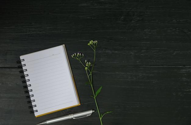 Vista superior do livro aberto. registre aberto com a pena no fundo de madeira e copie o espaço para o texto da inserção.
