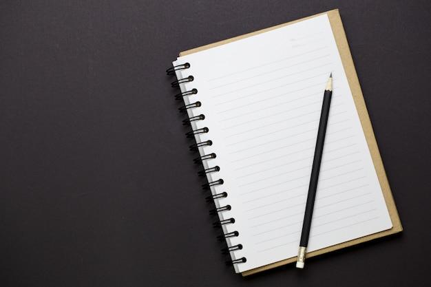 Vista superior do livro branco e lápis preto com espaço vazio para informações de texto