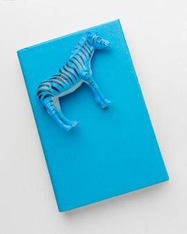 Vista superior do livro com estatueta de zebra no topo para o dia dos animais