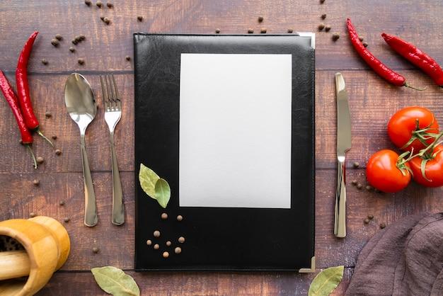 Vista superior do livro de menu com pimenta e talheres