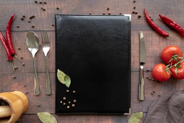 Vista superior do livro de menu com talheres e pimenta