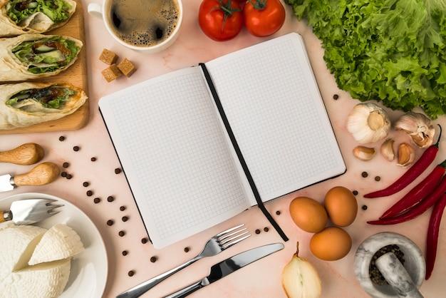 Vista superior do livro de menu vazio com salada e queijo