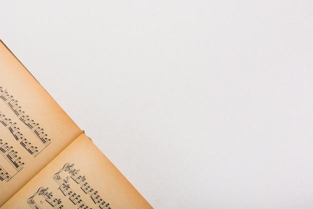 Vista superior do livro de nota musical vintage no fundo branco