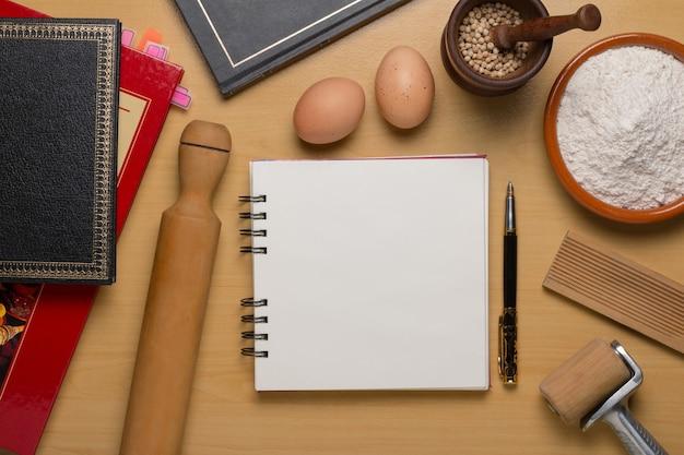 Vista superior do livro de receitas em branco aberto ao lado do conjunto de farinha de ovos e panelas