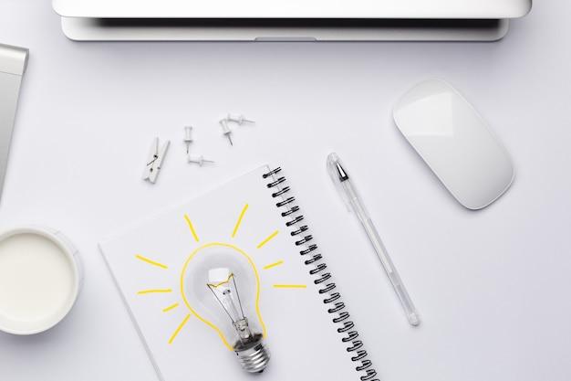 Vista superior do local de trabalho com uma lâmpada amarela como símbolo de uma ideia que se aproxima da criatividade