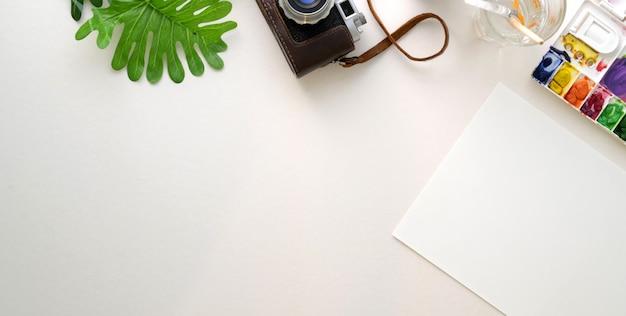 Vista superior do local de trabalho confortável artista com papel de desenho e ferramentas de pintura na mesa branca