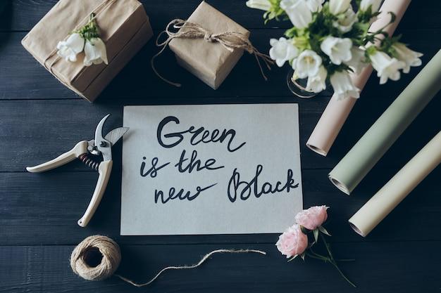 Vista superior do local de trabalho da loja de presentes com presentes embalados em papel kraft, rolos de papel de embrulho, podadores, barbante e cartão com a inscrição green is the new black