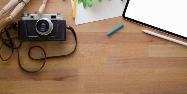 Vista superior do local de trabalho de design confortável com ferramentas de pintura e material de escritório na mesa de madeira